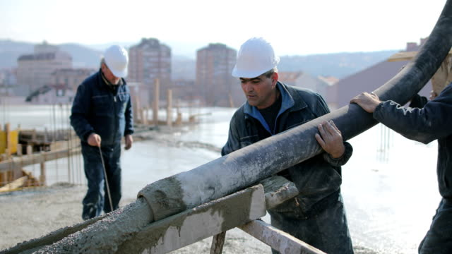 workers at the top of the building pouring concrete - work helmet stock videos & royalty-free footage