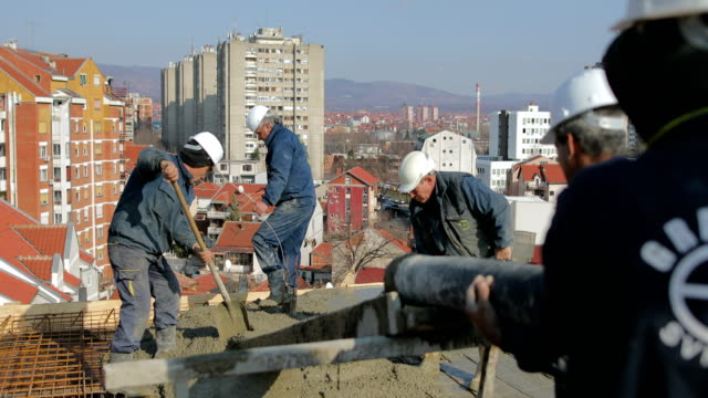 workers at the top of the building pouring concrete - building activity stock videos & royalty-free footage