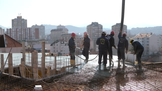 Workers at the top of the building pouring concrete