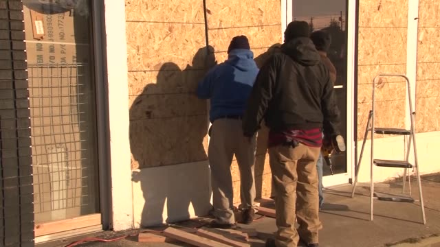 Workers board up the windows of their shops for possible protests after the Grand Jury releases their decision on whether or not to indict Officer...