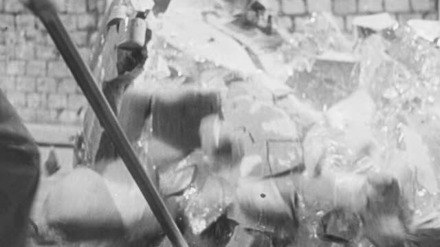 1951 montage workers breaking an optical glass mold then sorting through the pieces / united kingdom - 1951点の映像素材/bロール