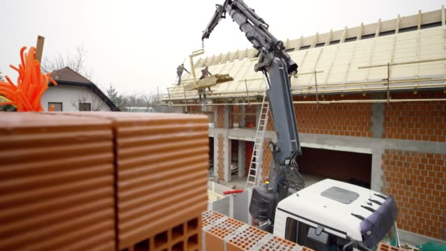 workers building a roof in the building site - crane stock videos & royalty-free footage