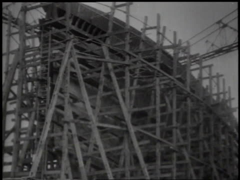1939 montage workers building a ship, with scaffolding around the boat and the boat launching into the water / japan - black and white stock videos & royalty-free footage