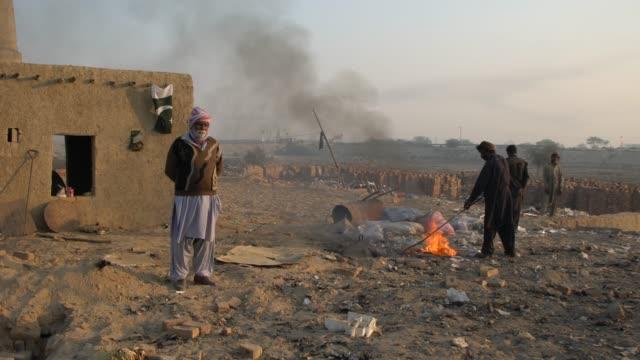 workers burning garbage at a brick kiln factory punjab, pakistan - pakistan stock videos & royalty-free footage