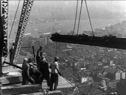 b/w 1930/31 workers by crane lifting beam in empire state bldg construction / nyc / industrial - kran stock-videos und b-roll-filmmaterial
