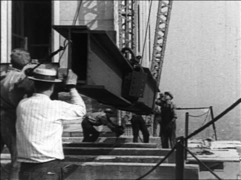 vidéos et rushes de b/w 1930/31 workers by crane lifting beam in empire state bldg construction / nyc / industrial - tour structure bâtie