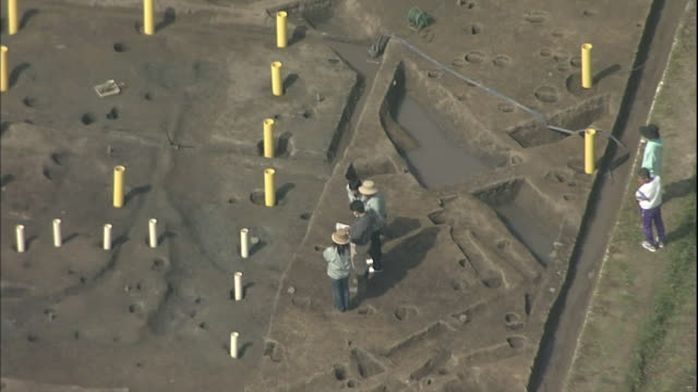 Workers check and note the position of a post hole at the Makimuku ruins in Nara, Japan.