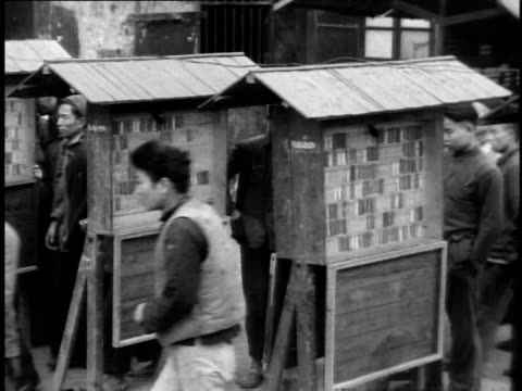 stockvideo's en b-roll-footage met 1944 ws workers checking in identification tags as they leave the factory after work / china - communisme