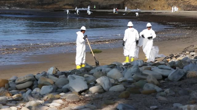 workers clean oil from an oil spill into the waters of the pacific ocean at refugio state beach on may 23 2015 in goleta california california gov... - environmental cleanup stock videos and b-roll footage