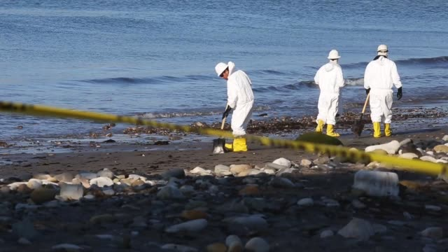 Workers clean oil from an oil spill into the waters of the Pacific Ocean at Refugio State Beach on May 23 2015 in Goleta California California Gov...