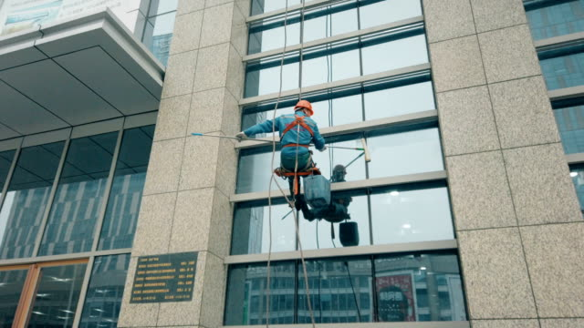 vidéos et rushes de workers cleaning exterior walls of building. - en verre