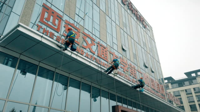 vídeos de stock e filmes b-roll de workers cleaning exterior walls of building. - chinese culture