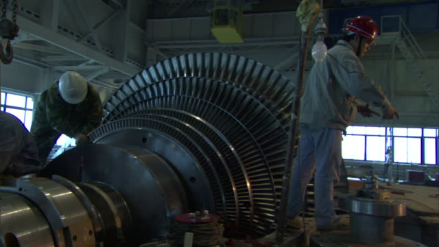 ms pan workers cleaning giant turbine inside coal fired power station, beijing, china - 発電所点の映像素材/bロール