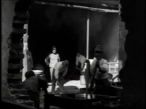 1938 ws workers cleaning up rubble, framed by large hole in damaged wall / japan - 1930~1939年点の映像素材/bロール