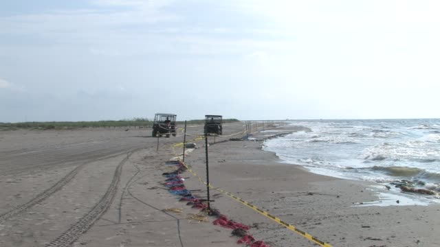workers cleaning up tarballs and oiled snare boom on port fourchon beaches oil containment snare boom on beach to catch oil coming in yellow... - environmental cleanup stock videos and b-roll footage