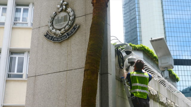 workers cleanup the hong kong police headquarters after thousands of protesters surrounded and cut it off for 15 hours the night before - cut video transition stock videos and b-roll footage