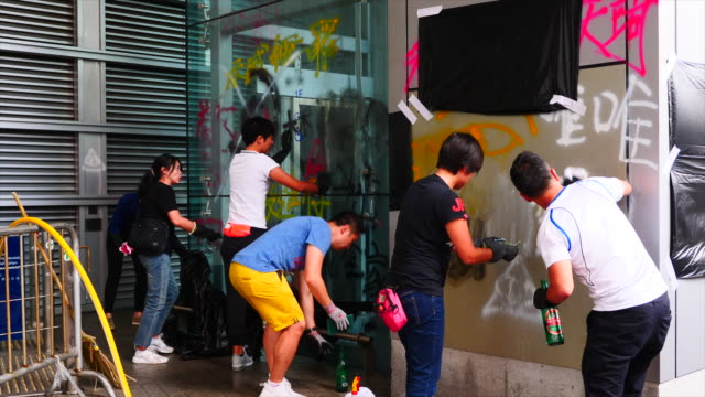 workers cleanup the hong kong police headquarters after thousands of protesters surrounded and cut it off for 15 hours the night before - umgeben stock-videos und b-roll-filmmaterial