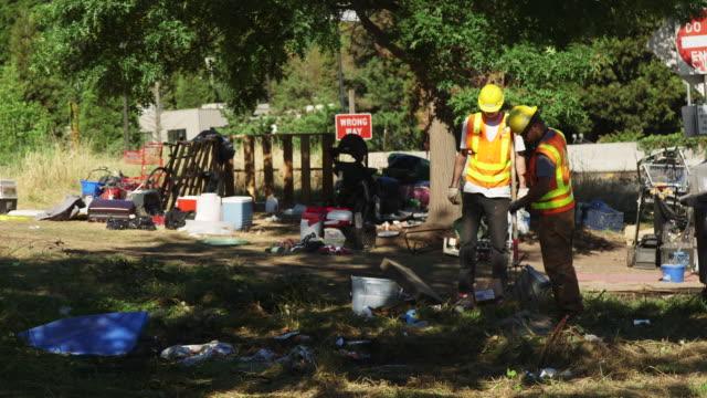 vídeos de stock e filmes b-roll de workers clear garbage in field - geleira portátil