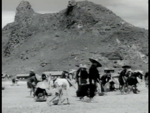 workers clearing area for use as landing field, runway, w/ tall rocks bg. workers picking up stones, rocks in cleared area, many chinese men pulling,... - farm worker stock videos & royalty-free footage