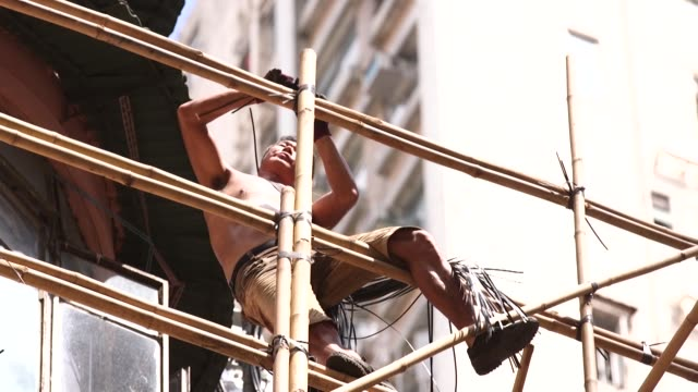 workers climb a bamboo scaffolding to secure bamboo poles with plastic fibre straps in the mong kok district of hong kong china on monday sept 12 a... - mong kok stock videos and b-roll footage