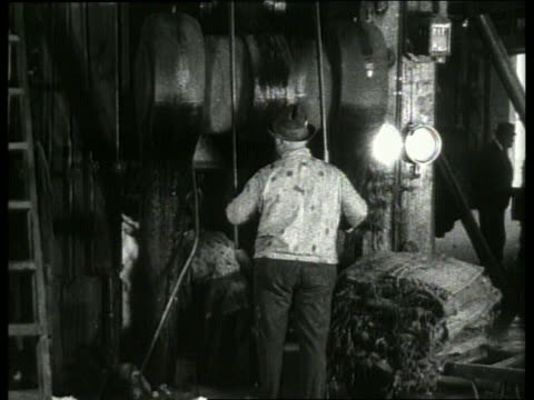 b/w workers compressing cotton bales in machine / 1910 new orleans / no sound - anno 1910 video stock e b–roll