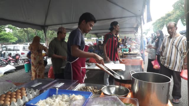 workers cook up food to sell to shoppers and pedestrians as they walk through a market in johor bahru johor malaysia on friday july 10 2015 shots... - newly industrialized country stock videos and b-roll footage