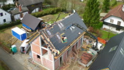 AERIAL Workers covering the roof of a new house