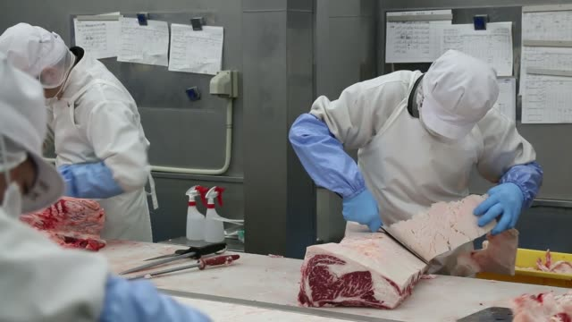 Workers cut beef slabs at a meat processing facility operated by Agris One Co a unit of Meat Companion Co in Wako Saitama Prefecture Japan on...