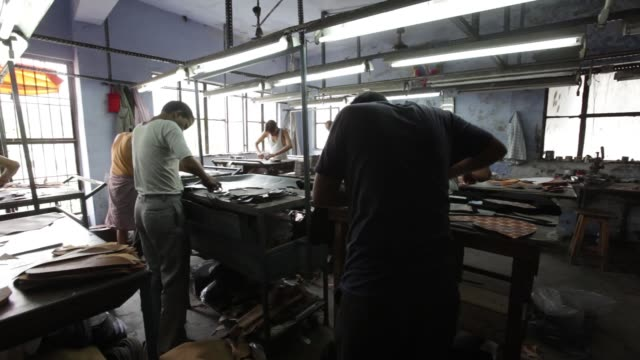 Workers cut designs from leather hides in the design section of a workshop in Agra Uttar Pradesh India on Wednesday June 21 CU a worker cuts designs...