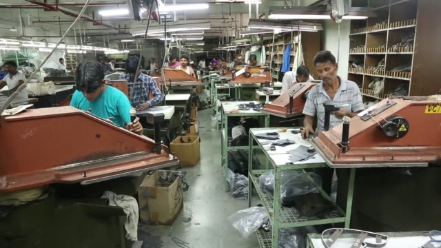 workers cut designs out of leather hides in the dye cutting section at a virola shoes pvt manufacturing facility in agra uttar pradesh india on... - 染料点の映像素材/bロール