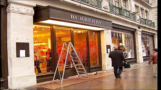 workers' demonstration outside regent street burberry store; tx burberry staff cleaning fake blood from store window after demonstration by animal... - animal blood stock videos & royalty-free footage