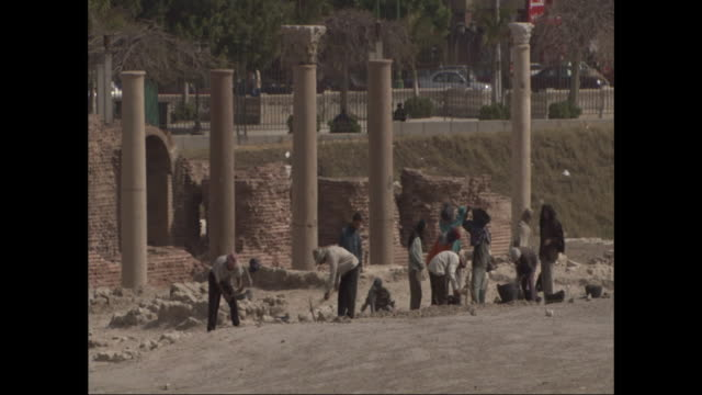 workers dig near ancient stone columns. - digging stock-videos und b-roll-filmmaterial