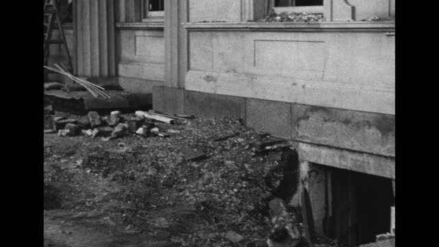 vidéos et rushes de workers digging in hole next to pile of dirt with pan to facade as they clean up after nazi bombings during the blitz on london of world war ii / vs... - creuser
