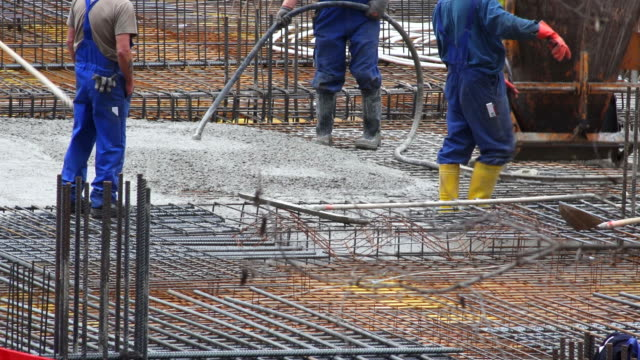 workers directing concrete onto the construction site - baugewerbe stock videos & royalty-free footage