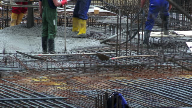 hd workers directing concrete onto the construction site - baugewerbe stock videos & royalty-free footage
