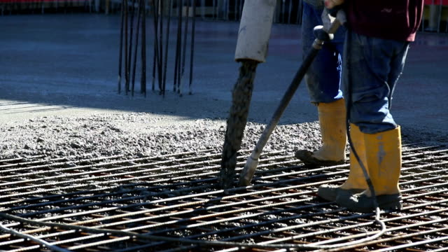 Lavoratori dirigere calcestruzzo in cantiere CU