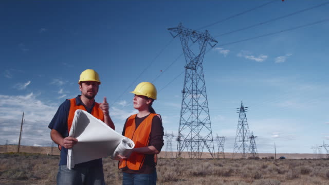 WS TU Workers discussing plans under power lines / Zillah, Washington, USA