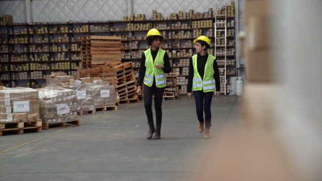workers discussing while walking in warehouse - reflective clothing stock videos & royalty-free footage