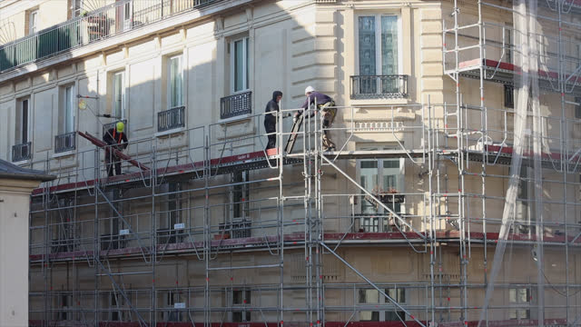 workers dismantle scaffolding on a parisian building - 足場点の映像素材/bロール