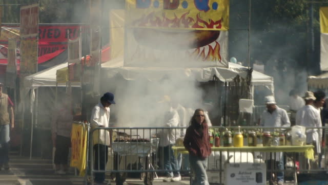 workers dressed in white cooking bbq at outdoor food stall emitting lots of smoke people walking past the food stall and in front of camera - emitting stock videos & royalty-free footage