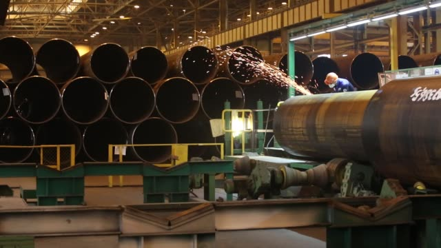 Workers expect the exterior and interior of large diameter steel pipes at the Izhora Pipe Mill operated by Severstal PJSC in the Kolpino district of...