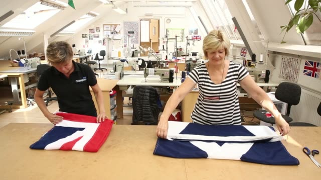 Workers fold a hand sewn British Union flag left and a Scottish St Andrews or Saltire flag right after completion at the Flagmakers workshop a unit...