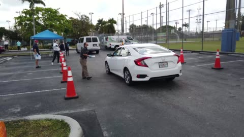 stockvideo's en b-roll-footage met workers for the city of hialeah hand out unemployment applications to people in their vehicles in front of the john f. kennedy library on april 08,... - werkloosheid
