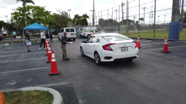 vídeos de stock e filmes b-roll de workers for the city of hialeah hand out unemployment applications to people in their vehicles in front of the john f kennedy library on april 08... - desemprego
