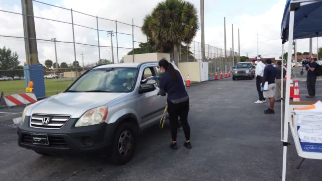 workers for the city of hialeah hand out unemployment applications to people in their vehicles in front of the john f kennedy library on april 08... - unemployment stock videos & royalty-free footage