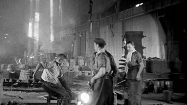 1940 MONTAGE Workers forging specialized tungsten steel in steel mill / United Kingdom