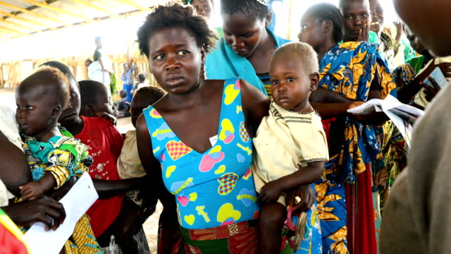 Workers from Action Africa Help screen refugees from the Democratic Republic of Congo for malnourishment in the Kyangwali Refugee Settlement on April...