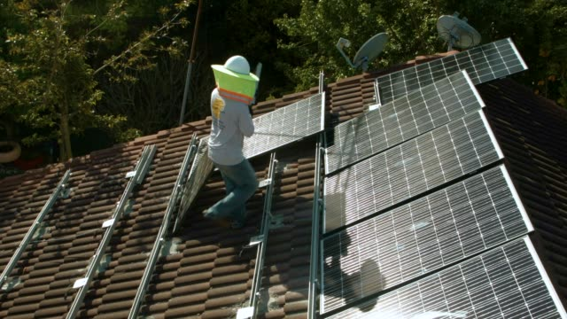 Workers from the Goldin Solar company install a solar panel system on the roof of a home a day after the Trump administration announced it will...