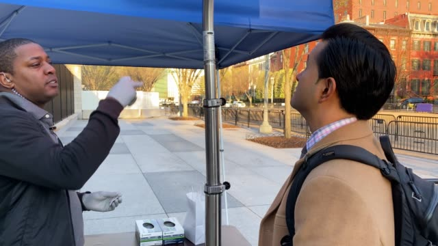 workers from the white house physician's office check the body temperatures of people entering the white house with a forehead temperature scanner on... - temperatur stock-videos und b-roll-filmmaterial