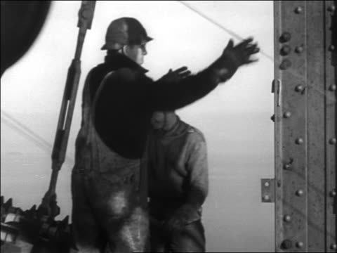 B/W 1936 2 workers grabbing wheel from cable / Golden Gate Bridge construction / SF / newsreel